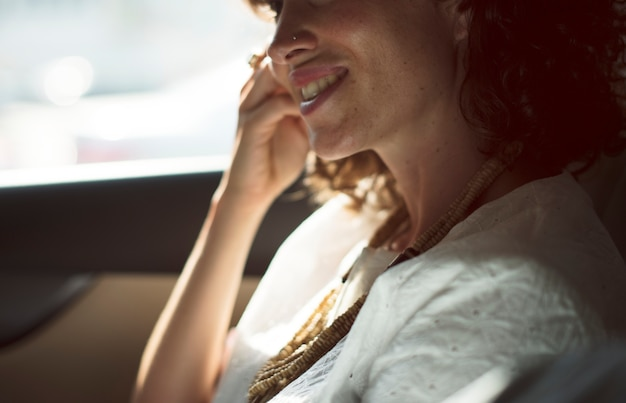 Businesswoman using mobile phone at back seat of the car