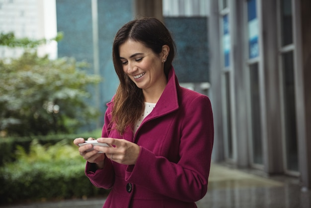 Businesswoman using phone outside office