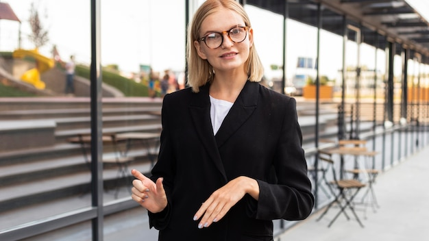Businesswoman using sign language outdoors at work