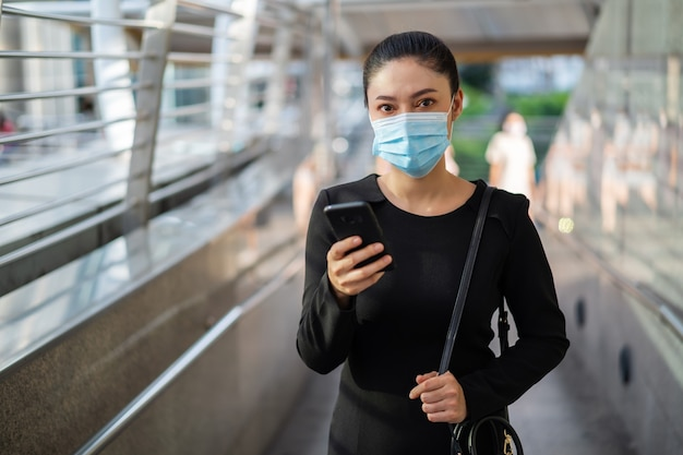 Деловая женщина с помощью смартфона и в медицинской маске