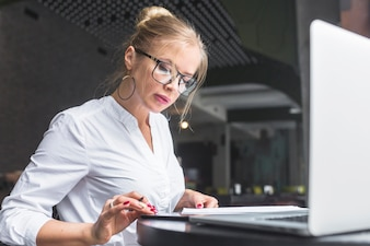Businesswoman using smartphone while making notes