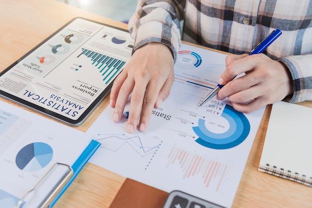 Donna d'affari che utilizza un tablet per analizzare il concetto di successo delle statistiche della strategia finanziaria aziendale del grafico e la pianificazione per il futuro nella stanza dell'ufficio.