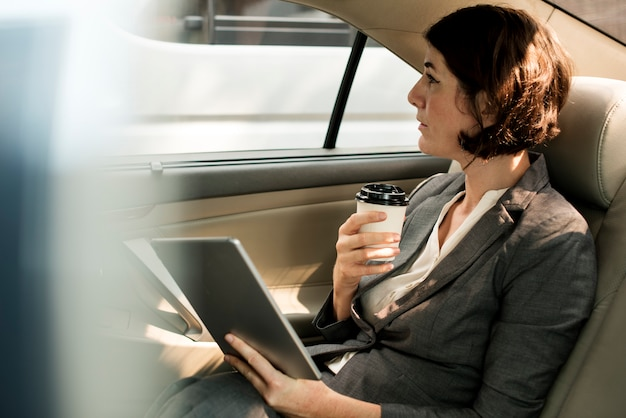 Businesswoman using tablet car inside