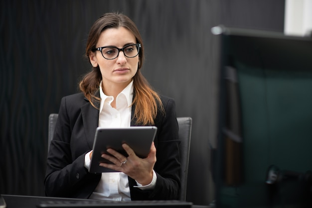 Businesswoman using a tablet in her company office, businesswoman career concept