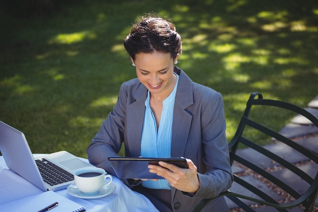Businesswoman using tablet with coffee