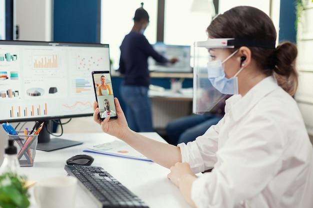 Деловая женщина с помощью беспроводных наушников во время онлайн-конференции на смартфоне в маске на рабочем месте. многонациональные коллеги, соблюдающие социальную дистанцию в бизнесе во время глобальной пандемии