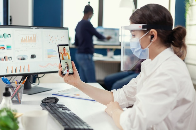 Businesswoman using wireless headphones during online conference on smartphone wearing face mask in workplace. multiethnic coworkers working respecting social distance in business during global pandem
