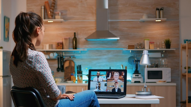 Businesswoman on video conference working remotely from home sitting in the kitchen late at night. lady using modern technology network wireless talking on virtual meeting at midnight doing overtime