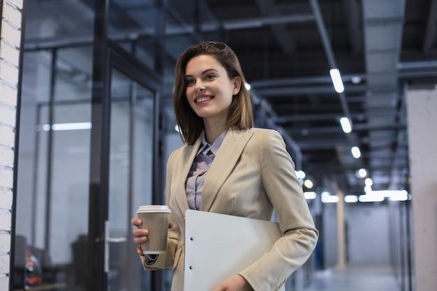 Деловая женщина, идущая по коридору офиса с документами и бумажным стаканчиком.