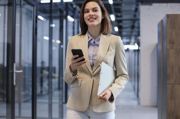 Деловая женщина идет по коридору офиса с документами и с помощью смартфона.