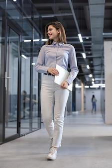 Деловая женщина идет по коридору офиса с документами.