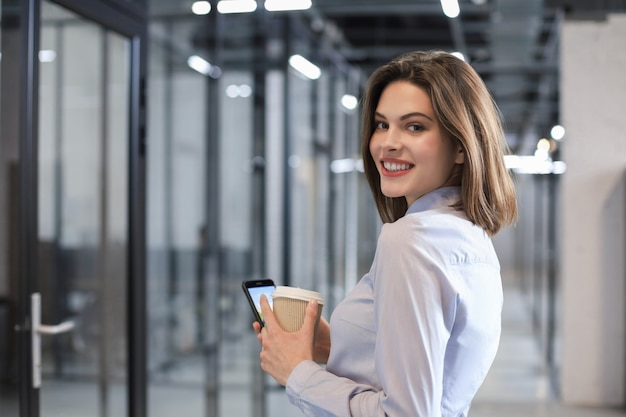 Деловая женщина, идущая по коридору офиса с бумажным стаканчиком и смартфоном.