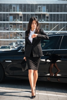 Businesswoman walking outdoors and looking at wristwatch Premium Photo