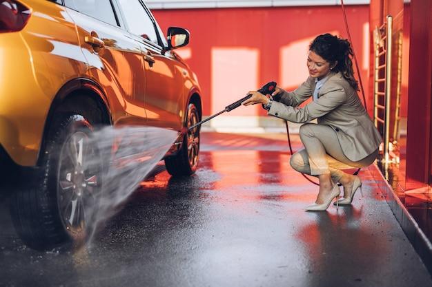 高圧水機を使用して洗車場で車を洗う実業家。