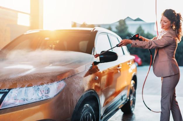 Предприниматель, моющий машину на станции мойки с использованием водяной машины высокого давления.