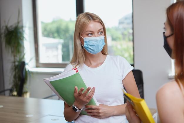 同僚と話している間保護フェイスマスクを身に着けている実業家