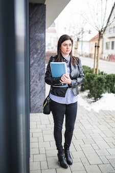 Businesswoman wearing black jacket with books standing on sidewalk