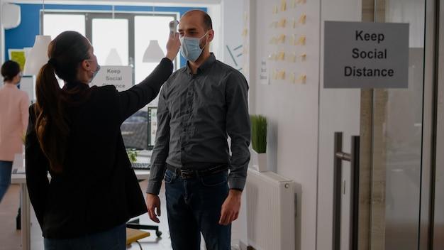ウイルス病を防ぐために温度計で労働者の温度をチェックするフェイスマスクを身に着けている実業家。コロナウイルスの世界的大流行に対して予防策を講じている事業会社