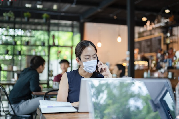 Businesswoman wearing face mask talking on cell phone working on laptop.