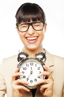 Businesswoman wearing glasses holding alarm clock
