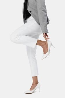 彼女の白いハイヒールを身に着けている実業家