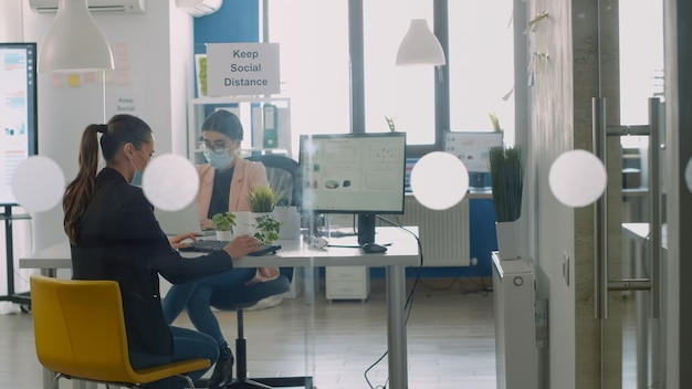 Businesswoman wearing protective face mask working on computer and discussing wiht collegue avout business job. coworkers keeping social distancing to avoid virus disease during global epidemic