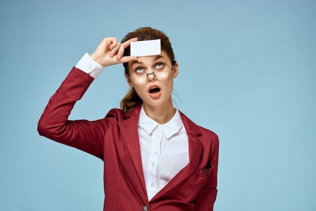 Деловая женщина в красной куртке держит визитную карточку на синем фоне.