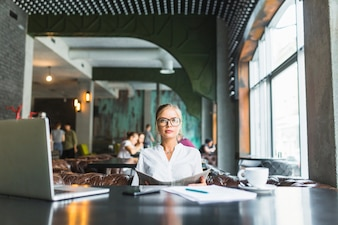 Businesswoman wearing spectacles holding newspaper in caf�