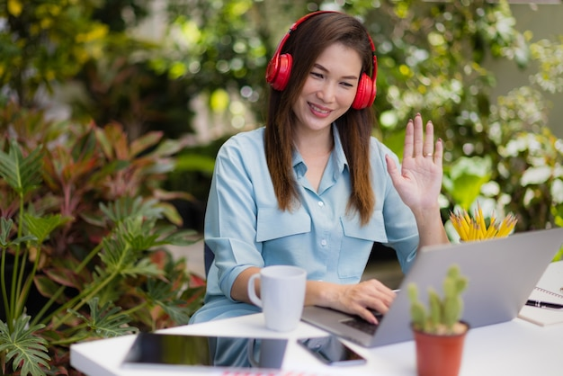 Businesswoman wears headphone sitting in house garden at working desk using laptop connect to online meeting and raises hand greeting for attendees. concept of new normal people and work at home.