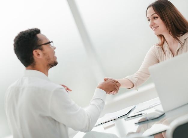 実業家は握手で彼女のビジネスパートナーを歓迎します。コピースペース付きの写真