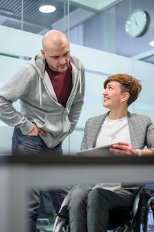Businesswoman in wheelchair talking to a man