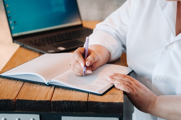 A businesswoman in a white shirt sits at a desk writing something in a notebook in the office.