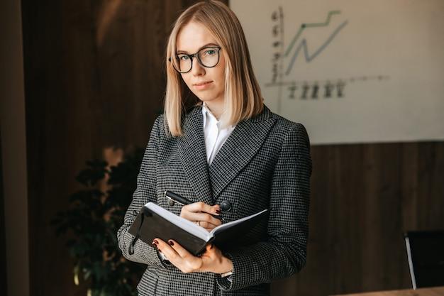 Деловая женщина с ноутбуком в руках стоит в офисе, глядя в окно.