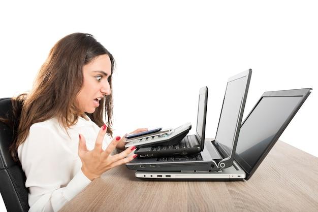 Деловая женщина с сердитым выражением лица и подчеркнула перед тремя ноутбуками
