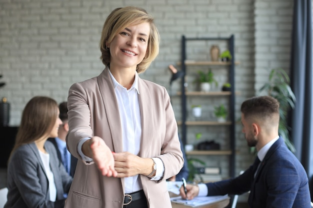 オフィスで握手の準備ができている開いた手を持つ実業家。