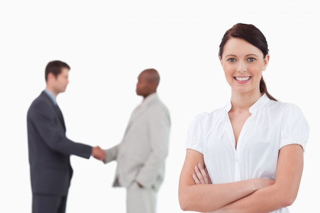Businesswoman with arms folded and hand shaking trading partners behind her