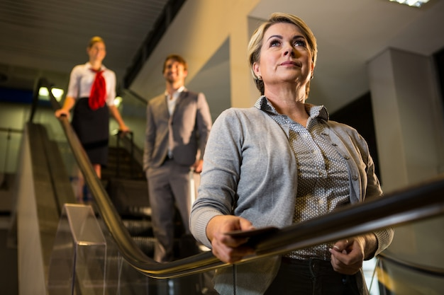Businesswoman with boarding pass on escalator