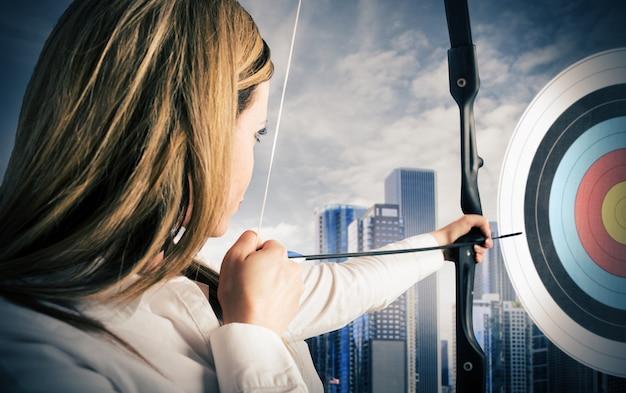 Деловая женщина с луком и стрелами, указывающая на центр цели