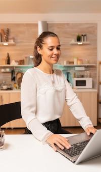 Donna d'affari con un programma fitto di appuntamenti che lavora al computer portatile a tarda notte per terminare la scadenza. imprenditore concentrato nella cucina di casa utilizzando il notebook durante le ore tarde la sera.
