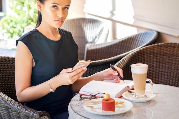 Деловая женщина с мобильным телефоном, сидя в кафе