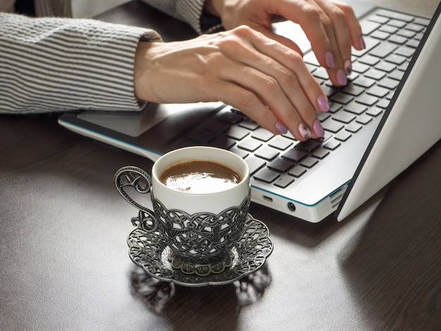 A businesswoman with a cup of coffee is typing on a laptop keyboard