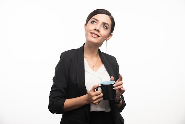 Imprenditrice con tazza e una matita su uno sfondo bianco. foto di alta qualità