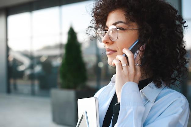 電話で話し合っているビジネスマンの外で電話をしている巻き毛の実業家