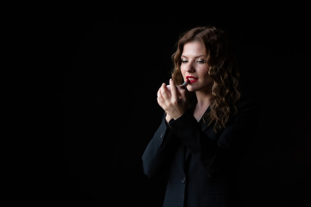 Businesswoman with curly hair paints lips with red lipstick isolated on black background