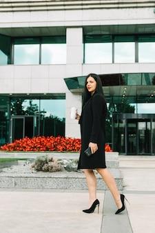 Donna di affari con la tazza di eliminazione che cammina davanti a costruzione