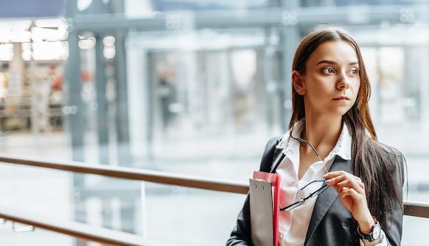 Деловая женщина с документами на работу. девушка-студентка с папками с документацией. офицер будет собирать информацию.