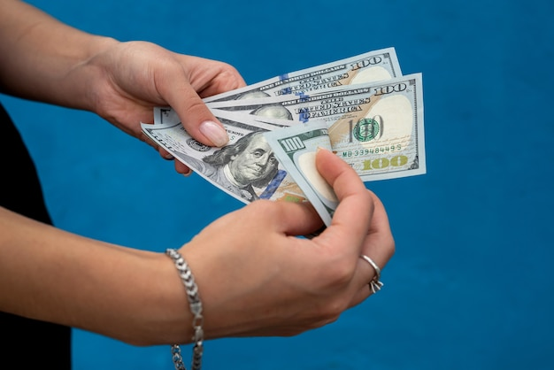 Businesswoman with dollars isolated on blue. finance concept