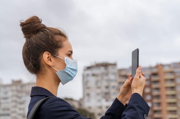 Imprenditrice con maschera facciale controllando il suo telefono