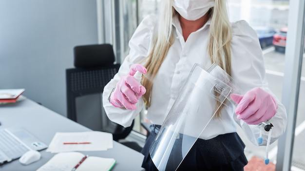 사무실에서 그녀의 얼굴 방패를 청소하는 동안 손 소독제를 사용하여 얼굴 마스크와 사업가. 보호 마스크를 착용하는 여자. 코로나 바이러스 예방.