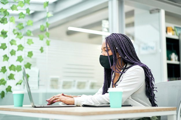 Businesswoman with a facial mask sitting at office desk holding coffee